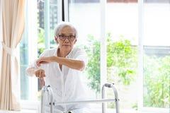 Azjatyccy starszy ludzie siedzie? relaksuj? z piechurem podczas rehabilitacji, starszych kobiety odzie?y szkie?, ?wiczenia i patr zdjęcia stock