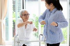 Azjatyccy starszy ludzie siedzie? relaksuj? z piechurem, starsz? kobieta, macierzysty ono u?miecha si?, ?wiczenie podczas, lub i  zdjęcia stock