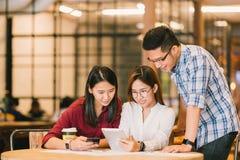 Azjatyccy studenci collegu lub coworkers używa wpólnie przy sklep z kawą cyfrową pastylkę i smartphone obraz royalty free