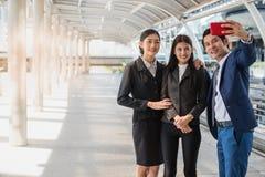 Azjatycka biznes drużyna bierze selfie z smartphone w mieście, Zdjęcia Stock