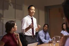 Azjatycka biznesmen pozycja adresować kolegów przy spotkaniem obrazy stock