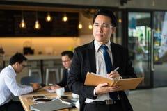 Azjatycka biznesmen pozycja, mienie i książka, myśleć i pisze planie biznesowym obraz royalty free