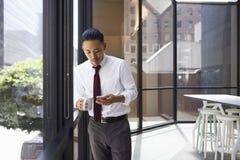 Azjatycka biznesmen pozycja w nowożytnym biurowym używa telefonie obraz stock