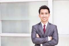 Azjatycka biznesmen pozycja zbroi krzyżuje i ono uśmiecha się Zdjęcie Stock