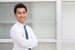 Azjatycka biznesmen pozycja zbroi krzyżuje i ono uśmiecha się Obraz Royalty Free