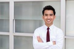 Azjatycka biznesmen pozycja zbroi krzyżuje i ono uśmiecha się Zdjęcie Royalty Free