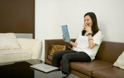 Azjatycka biznesowa kobieta śmia się przed pastylką w żywym pokoju zdjęcia royalty free