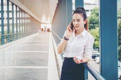 Azjatycka biznesowa kobieta jest ubranym białego koszulowego opowiada smartphone dla Zdjęcie Stock