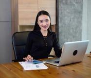 Azjatycka biznesowa kobieta siedzi na krześle i pracuje z komputerem i pastylką Obrazy Royalty Free