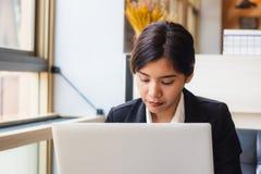 Azjatycka biznesowa kobieta używa laptop sprawdza emaila, wiadomości w lub Zdjęcia Stock