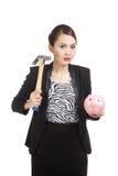 Azjatycka biznesowa kobieta z świniowatym menniczym bankiem i młotem Fotografia Stock