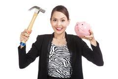 Azjatycka biznesowa kobieta z świniowatym menniczym bankiem i młotem Obrazy Stock