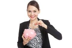 Azjatycka biznesowa kobieta z monetą i świniowatym menniczym bankiem Fotografia Royalty Free