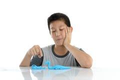 Azjatycka chłopiec bawić się błękitną glinę na bielu Fotografia Royalty Free