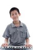 Azjatycka chłopiec bawić się klawiaturę na bielu Obrazy Stock
