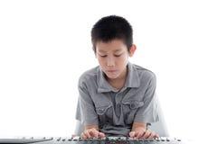 Azjatycka chłopiec bawić się klawiaturę na bielu Obraz Stock