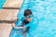 Azjatycka chłopiec jest ubranym wodoodpornych okulary przeciwsłonecznych próbuje pływackiego w sw samotnie zdjęcia royalty free