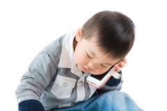 Azjatycka chłopiec opowiada dzwonić obraz stock