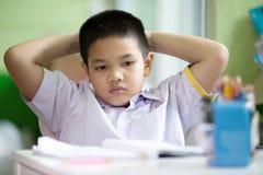 Azjatycka chłopiec robi jego pracie domowej zanudzał Obrazy Royalty Free