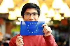 Azjatycka chłopiec trzyma flaga Europe zjednoczenie w szkłach Zdjęcia Royalty Free