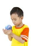 Azjatycka chłopiec trzyma nasz planety ziemię w jego ręce. Zdjęcia Stock