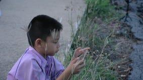 Azjatycka chłopiec trzyma obsiadanie na ulicznym tle i telefon drogi i trawa zbiory