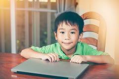 Azjatycka chłopiec używał nowożytną pokolenie technologię z laptopem Obrazy Royalty Free
