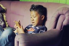 Azjatycka chłopiec zaskakiwał widzieć coś na handphone obrazy stock