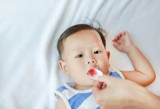 Azjatycka ch?opiec bierze medycyna syrop od ?y?ki dziecko jest chore fotografia stock