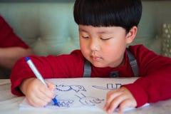 Azjatycka chłopiec rysuje obrazek Obraz Stock