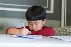 Azjatycka chłopiec rysuje obrazek Zdjęcie Stock