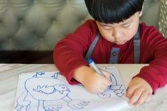 Azjatycka chłopiec rysuje obrazek Zdjęcie Royalty Free