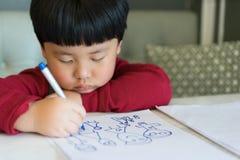 Azjatycka chłopiec rysuje obrazek Zdjęcia Royalty Free