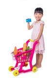 Azjatycka Chińska mała dziewczynka trzyma kredytową kartę z zakupy trol Zdjęcia Stock