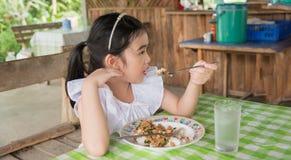 Azjatycka dzieciak dziewczyny łasowania basilu wieprzowina w Tajlandia Obrazy Stock