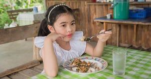 Azjatycka dzieciak dziewczyny łasowania basilu wieprzowina w Tajlandia Zdjęcia Royalty Free