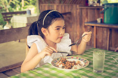 Azjatycka dzieciak dziewczyny łasowania basilu wieprzowina w Tajlandia Obraz Royalty Free