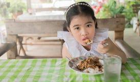 Azjatycka dzieciak dziewczyny łasowania basilu wieprzowina w Tajlandia Fotografia Royalty Free