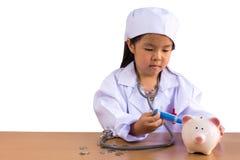 Azjatycka dziewczyna bawić się jako doktorski opieki prosiątka bank, odosobniony backgro fotografia stock