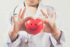 Azjatycka dziewczyna bawić się jako doktorskiej opieki zdrowy serce Obrazy Stock