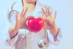 Azjatycka dziewczyna bawić się jako doktorskiej opieki zdrowy serce Zdjęcia Stock