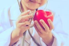 Azjatycka dziewczyna bawić się jako doktorskiej opieki zdrowy serce Fotografia Royalty Free