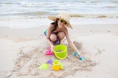 Azjatycka dziewczyna bawić się piasek na plaży fotografia stock