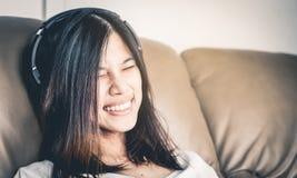 Azjatycka dziewczyna jest śmiechem i ono uśmiecha się podczas gdy słuchający muzyka zdjęcia stock