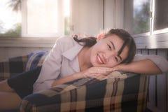 Azjatycka dziewczyna jest uśmiechnięta i będąca usytuowanym w leżance, kłama na kanapie obrazy royalty free