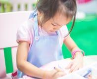 Azjatycka dziewczyna jest ubranym fartucha uczenie sztukę Obraz Stock