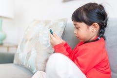 Azjatycka dziewczyna patrzeje mądrze obsiadanie na kanapie i telefon fotografia royalty free