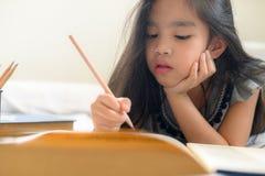 Azjatycka dziewczyna pisze z ołówkiem i notatnikiem zdjęcie stock