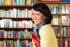 Azjatycka dziewczyna przy bibliotecznym mieniem książka Zdjęcia Stock