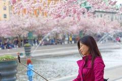 Azjatycka dziewczyna różowię suknię bierze selfie wśród pięknego blo Obrazy Stock